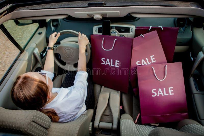 Een meisje met het winkelen zakken drijft een auto, concept kortingen en winkelt, hoogste mening stock afbeelding