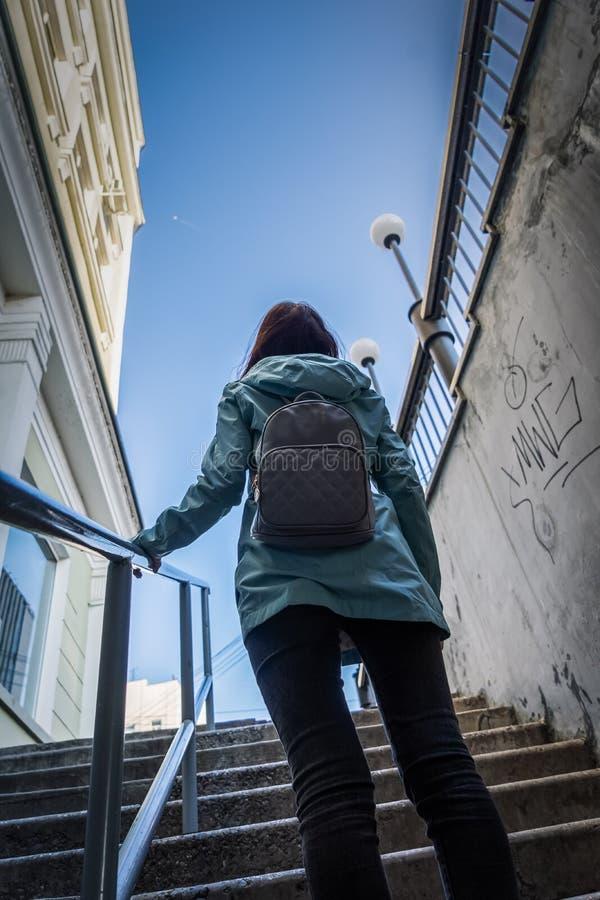 Een meisje met een kleine stadsrugzak loopt uit de metro, uit dark, in het licht en klampt zich aan de leuning vast stock fotografie