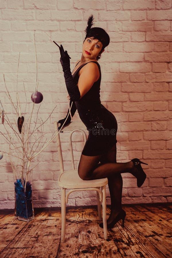 Een meisje met kort zwart haar met een verband met lovertjes en veren op haar hoofd in een kleding met lovertjes in Chicago stock afbeelding
