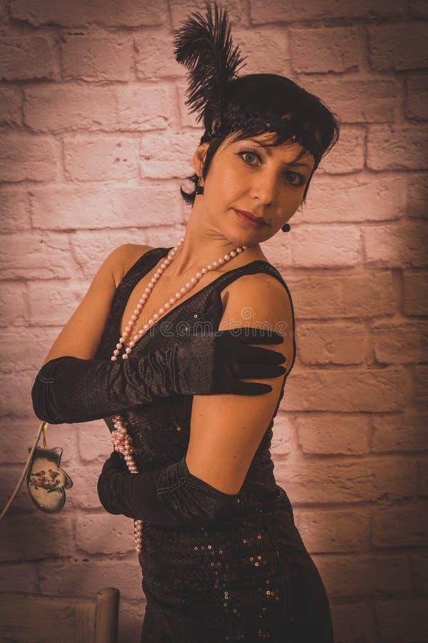 Een meisje met kort zwart haar met een verband met lovertjes en veren op haar hoofd in een kleding met lovertjes in Chicago stock afbeeldingen