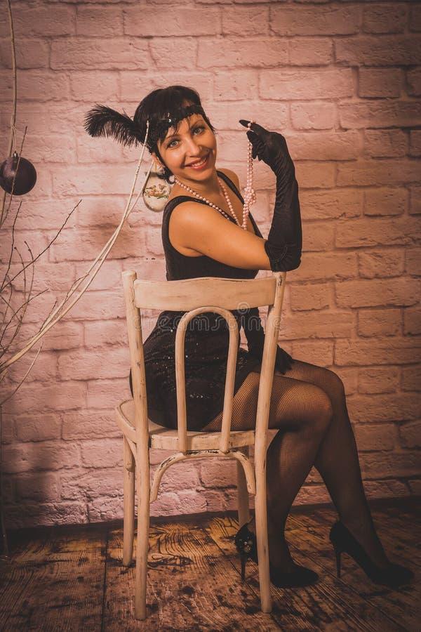 Een meisje met kort zwart haar met een verband met lovertjes en veren op haar hoofd in een kleding met lovertjes in Chicago stock fotografie