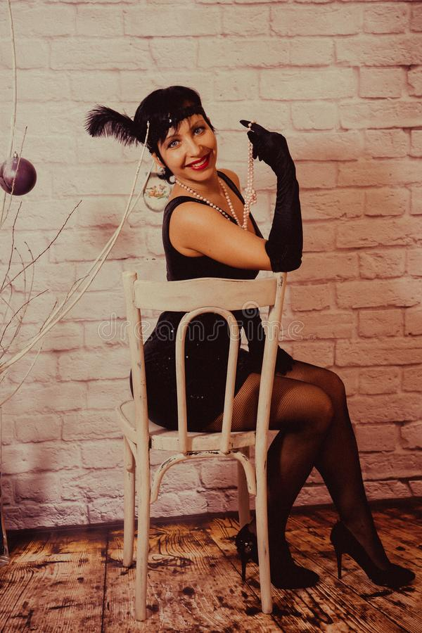 Een meisje met kort zwart haar met een verband met lovertjes en veren op haar hoofd in een kleding met lovertjes in Chicago royalty-vrije stock afbeeldingen