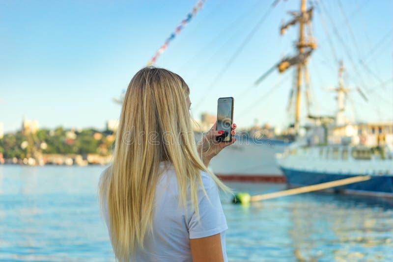Een meisje met lang blond haar gaat achteruit stock afbeelding