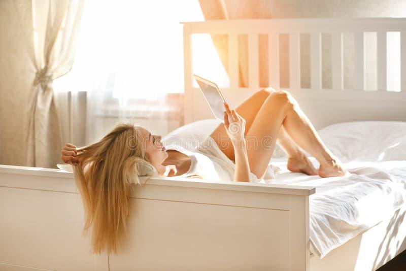 Een meisje met lang haar ligt op haar bed in een ruimte met een ipad stock foto