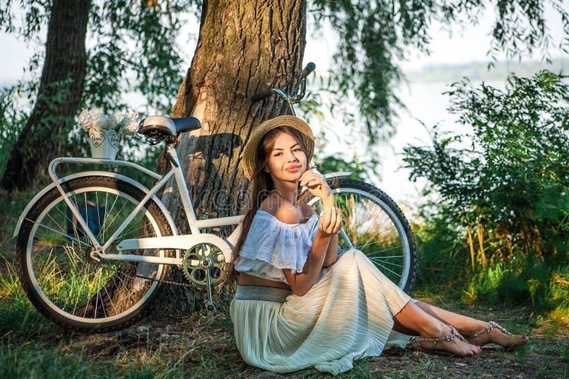 Een meisje met mollige lippen in een strohoed zit op de rivierbank royalty-vrije stock afbeelding