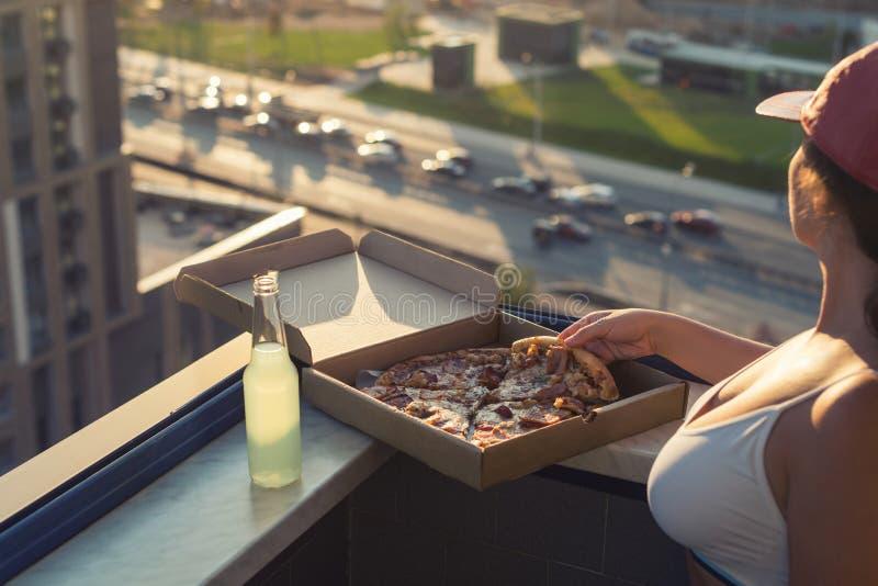 Een meisje met een mooie borst in een sportenkostuum gaat pizza en drankmojito op de achtergrond van de zonsondergangstad eten stock fotografie