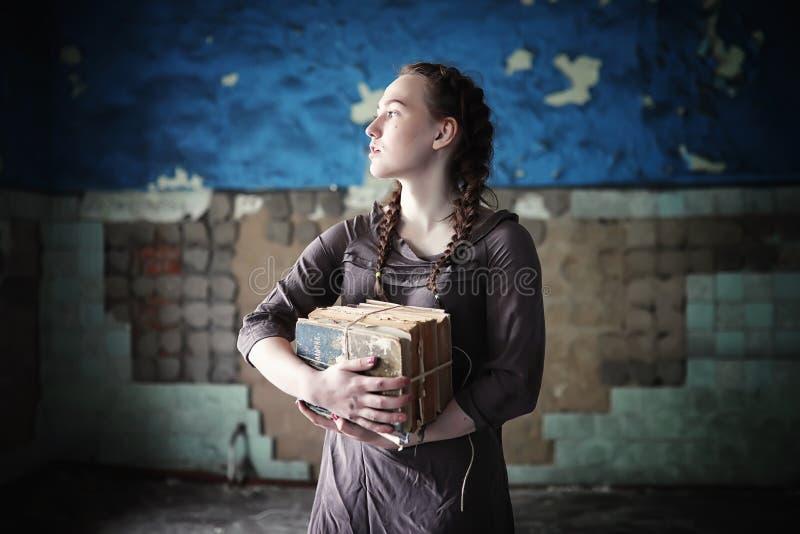 Een meisje met oude boeken in het oude huis royalty-vrije stock afbeelding