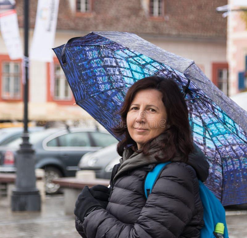 Een meisje met paraplubakken op een regenachtige dag op een straat in Sibiu stad in Roemenië stock foto's