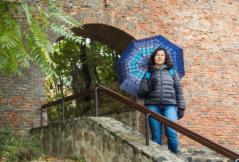 Een meisje met paraplubakken op een regenachtige dag op een trap dichtbij de doorgang in de stadsmuur in Sibiu stad in Roemenië stock foto's