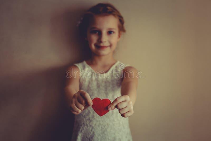 Een meisje met rood hart in haar handen royalty-vrije stock afbeeldingen