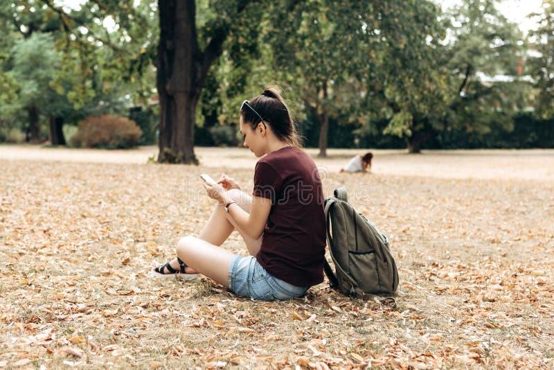 Een meisje met een rugzak zit in een de herfstpark en gebruikt een celtelefoon stock foto