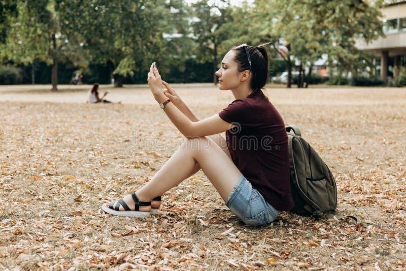 Een meisje met een rugzak zit in een de herfstpark en gebruikt een celtelefoon royalty-vrije stock foto