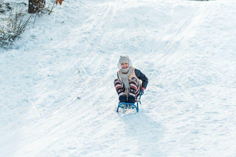 Een meisje met slee Mooie tiener die pret buiten in een hout met sneeuw in de winter hebben actief het levensconcept royalty-vrije stock afbeelding