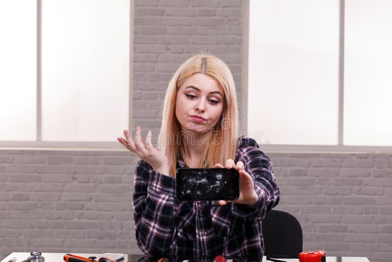 Een meisje met teleurgesteld kijkt bekijkt een smartphone met het gebroken scherm dat ter beschikking houdt royalty-vrije stock fotografie