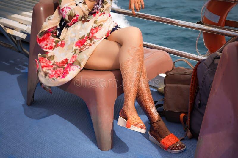 Een meisje met tijdelijke hennatatoegeringen op haar benen Zit in kleurrijke kleding op een stoel op een cruiseschip stock foto's