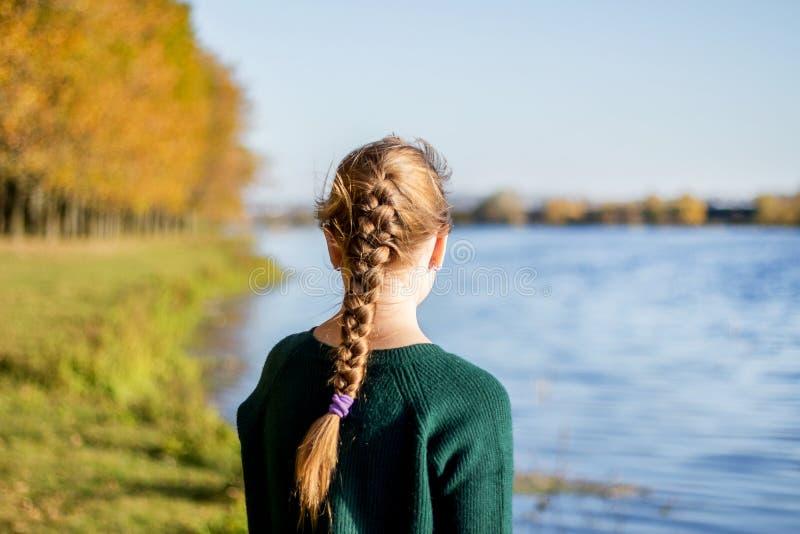 Een meisje met een vlecht bevindt zich op de rivierbank in autumn_ stock afbeeldingen