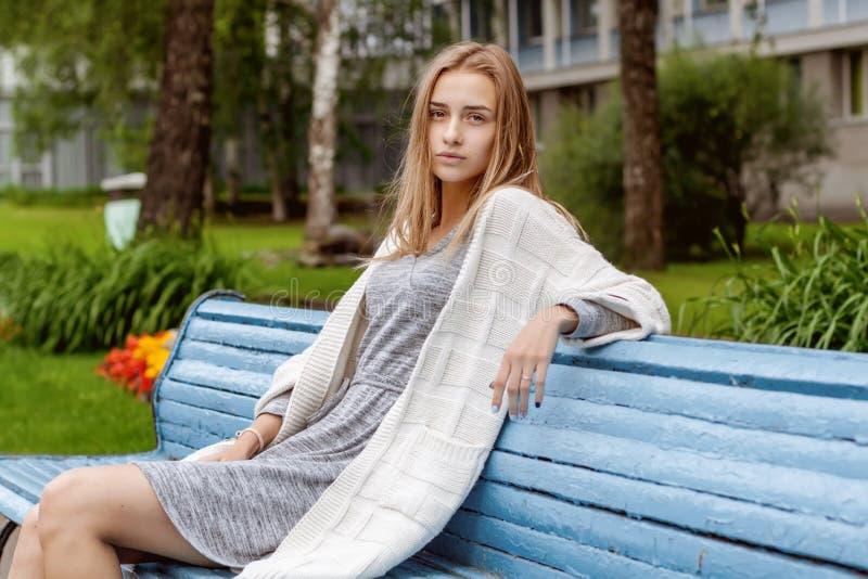 Een meisje in modieuze kleren en mooie blikken zit op een blauwe bank in een de zomerpark stock afbeelding