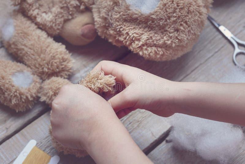 Een meisje naait een beerstuk speelgoed Ambacht met kinderen Het kind vult het stuk speelgoed met een sintepon toning stock foto's