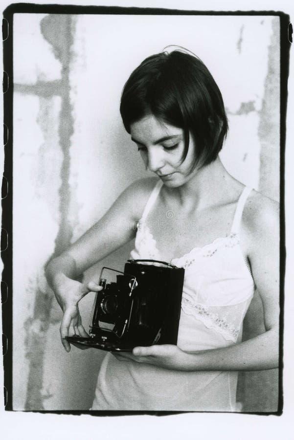 Een meisje in een nachtjapon houdt een groot formaat uitstekende camera stock afbeeldingen