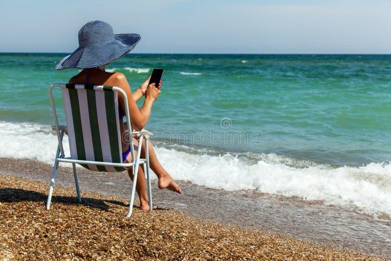 Een meisje op een strand werkt aan een telefoon stock foto's