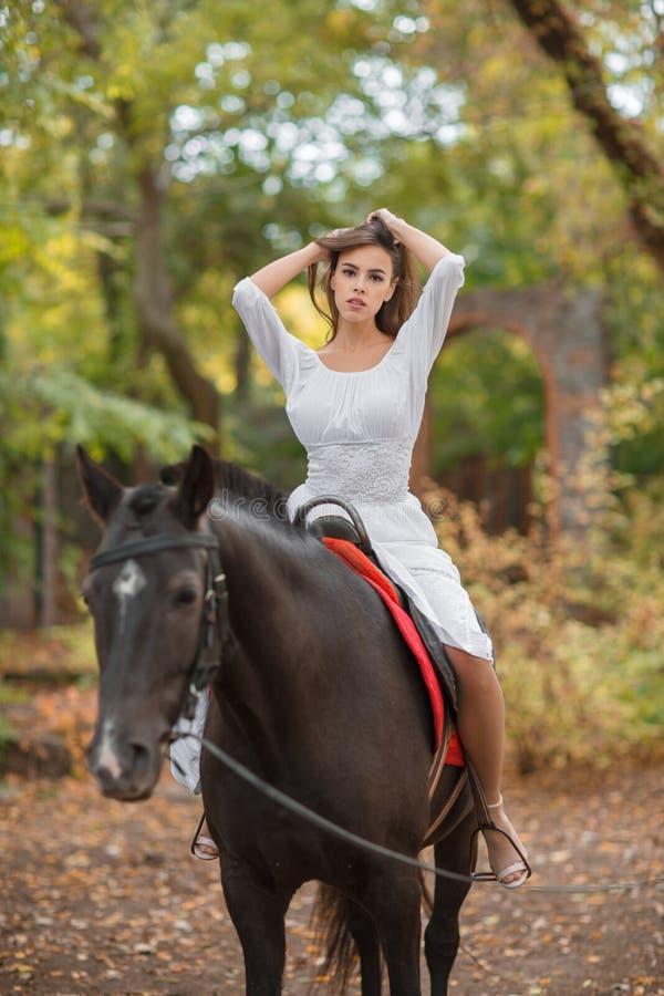 Een meisje op een paard maakt haar haar recht royalty-vrije stock afbeeldingen