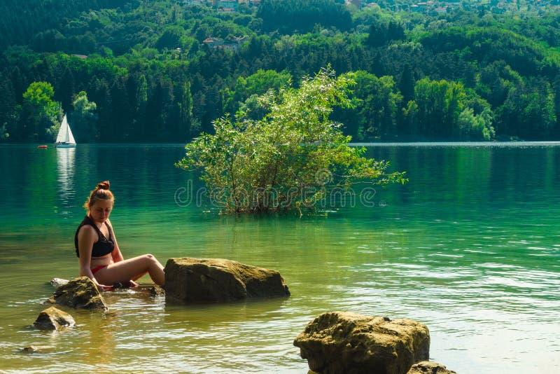 Een meisje op een rots in het meer, op achtergrond een zeilboot stock fotografie