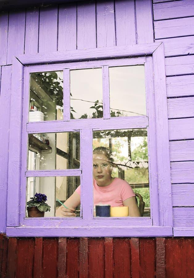 Een meisje in een oud landelijk huis dat door het venster kijkt royalty-vrije stock foto's