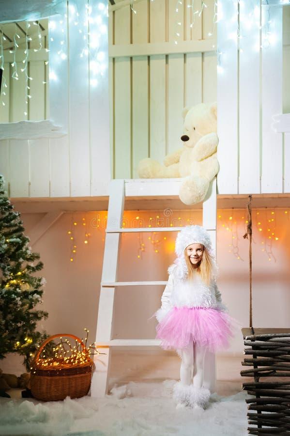Een meisje in een poedelkostuum voor het Nieuwjaar Het meisje bevindt zich op de portiek van een wit verfraaid blokhuis royalty-vrije stock foto's