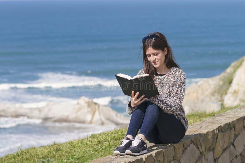Een meisje readingh door de kust royalty-vrije stock foto