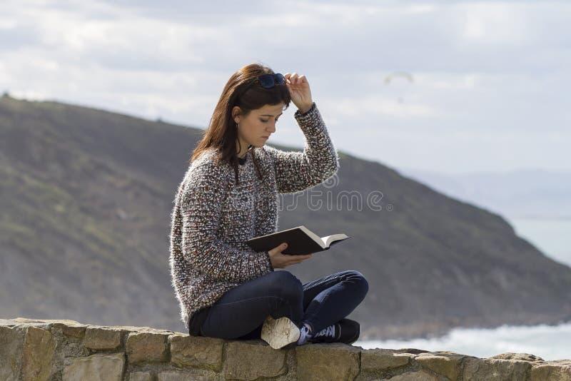 Een meisje readingh door de kust royalty-vrije stock foto's