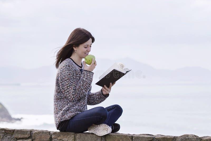Een meisje readingh door de kust stock afbeeldingen
