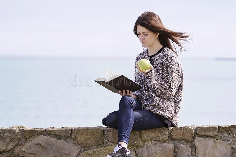 Een meisje readingh door de kust royalty-vrije stock afbeeldingen
