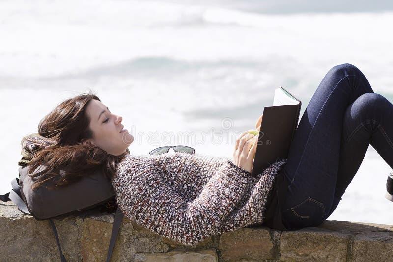 Een meisje readingh door de kust stock foto