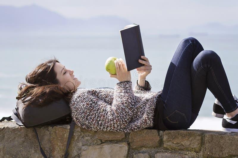 Een meisje readingh door de kust royalty-vrije stock fotografie