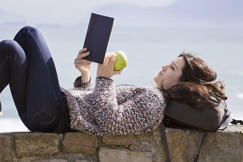 Een meisje readingh door de kust stock fotografie