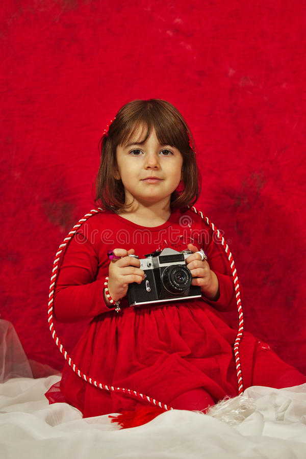Een meisje in rood die een uitstekende fotocamera met behulp van royalty-vrije stock fotografie