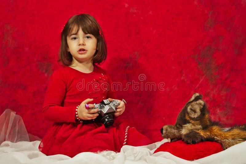 Een meisje in rood die een uitstekende fotocamera met behulp van royalty-vrije stock foto