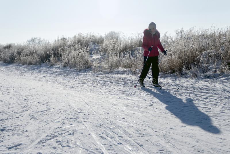 Een meisje in een rood jasje en zwarte broek op skis in het ochtendlicht Sneeuwachtergrond met slepen, schaduw van vrouw en copys stock fotografie
