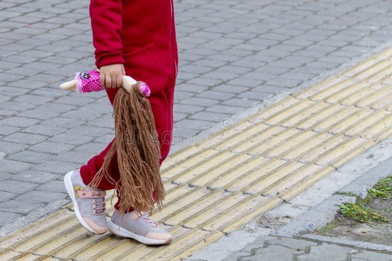 Een meisje in een rood kostuum met een pop met lang haar in haar hand loopt langs de stoep stock fotografie