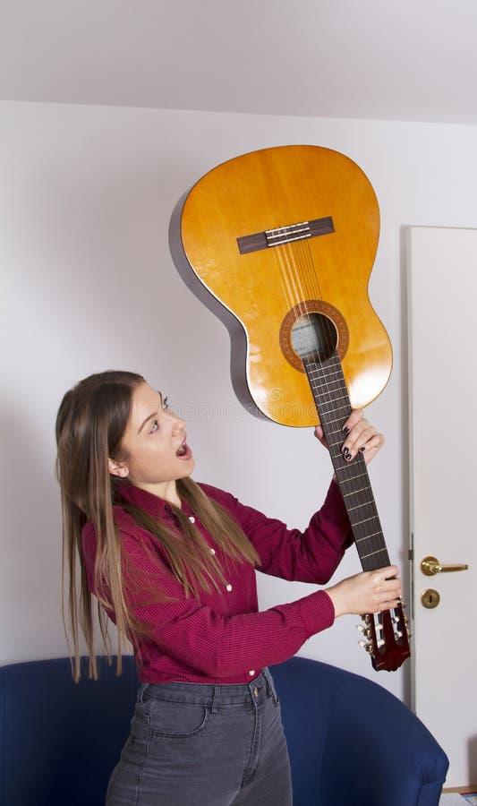 Een meisje in een rood overhemd houdt een akoestische gitaar en wil het breken stock foto's