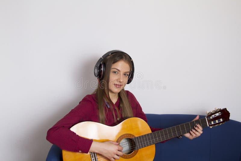 Een meisje in een rood overhemd Houdt een akoestische gitaar en wil spelen stock afbeeldingen