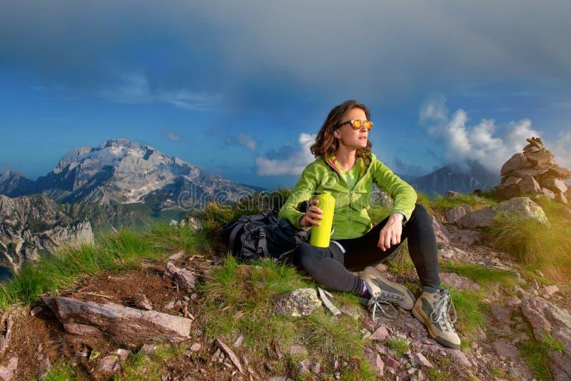 Een meisje rust na het beklimmen van de bovenkant van een berg stock foto's
