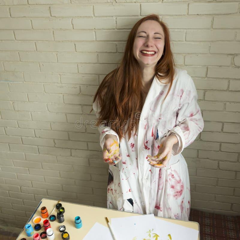 Een meisje schildert beeld met kleuren gebruikend haar eigen handen royalty-vrije stock afbeelding