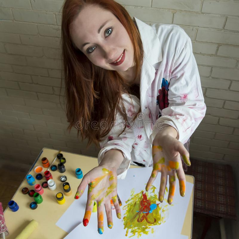 Een meisje schildert beeld met kleuren gebruikend haar eigen handen royalty-vrije stock foto's