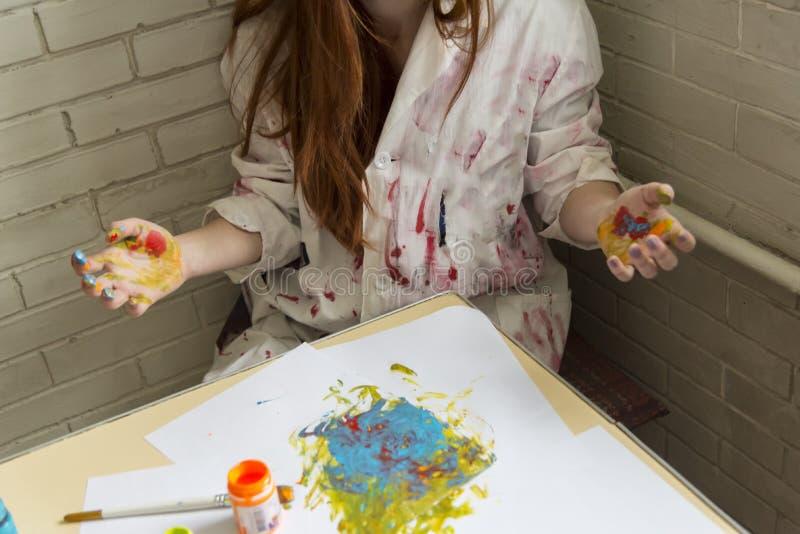 Een meisje schildert beeld met kleuren gebruikend haar eigen handen royalty-vrije stock afbeeldingen