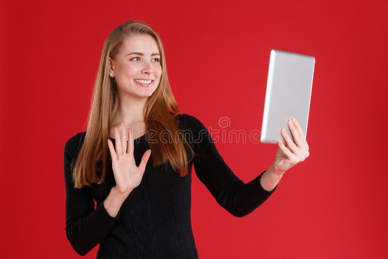 Een meisje spreekt aan iemand via videomededeling door een tablet en cheerfully handen royalty-vrije stock afbeelding