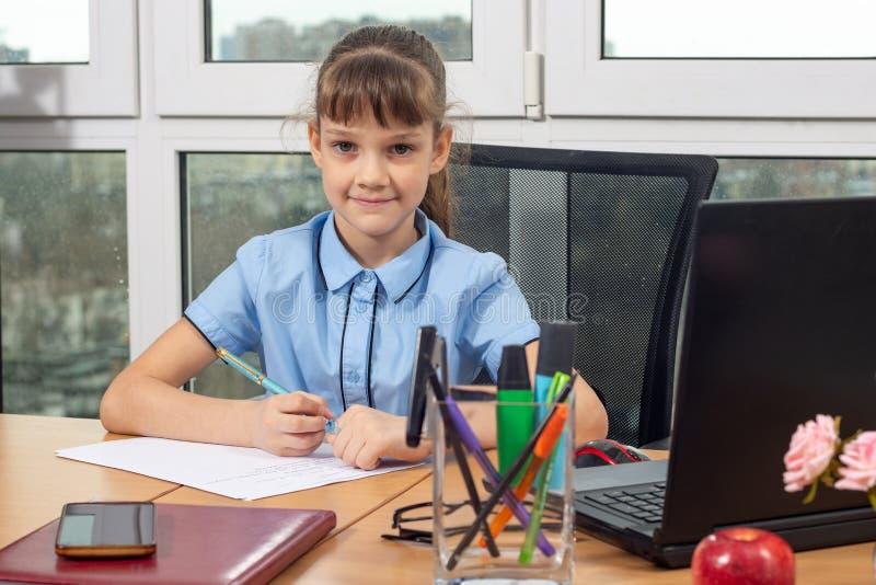 Een meisje van acht jaar oud bij de lijst in de bureauspelen in de bureauwerknemer royalty-vrije stock foto