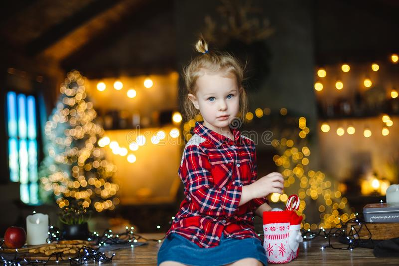 Een meisje van de blondepeuter in een geruit rood overhemd neemt suikergoed van een zoete Kerstmisgift royalty-vrije stock foto