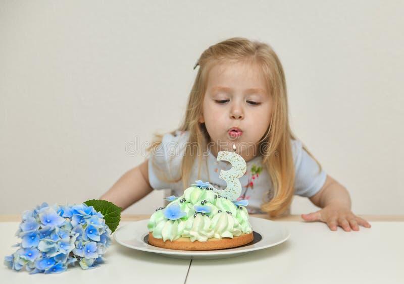 Een meisje van 3 jaar oude het maken wens blazende kaarsen op de blauwe cake royalty-vrije stock foto