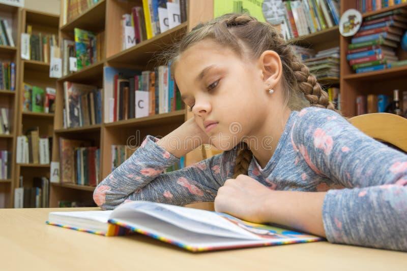 Een meisje van tien jaar oud leest een boek in de lezingsruimte royalty-vrije stock afbeelding